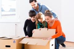 Familj som packar upp flyttande askar i nytt hem Royaltyfri Bild