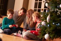 Familj som packar upp gåvor vid julgranen Royaltyfri Fotografi