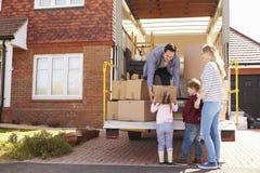 Familj som packar upp inflyttningaskar från borttagningslastbilen royaltyfria foton