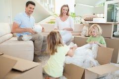 Familj som packar upp kartongen i vardagsrumet Royaltyfri Foto
