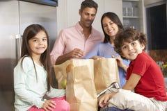 Familj som packar upp livsmedelsbutikshopping i kök arkivfoto