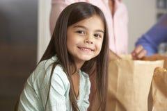 Familj som packar upp livsmedelsbutikshopping i kök arkivbild