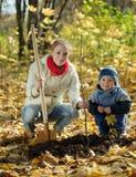Familj som planterar treen i höst Royaltyfri Fotografi