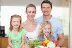 Familj som plattforer i kök Fotografering för Bildbyråer