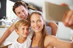 Familj som poserar för Selfie på frukosttabellen royaltyfria foton