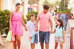 Familj som promenerar gatan med shoppingpåsar royaltyfri bild