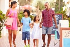 Familj som promenerar gatan med shoppingpåsar arkivfoto