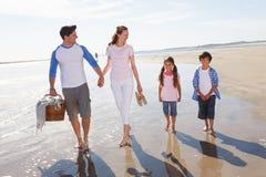 Familj som promenerar stranden med picknickkorgen Arkivfoton
