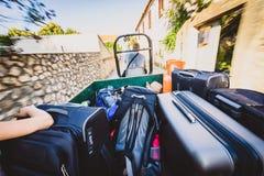 Familj som rider en traktorsläp med resväskor och bagage royaltyfria foton