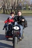 Familj som rider en tre rullad cykel Arkivbild