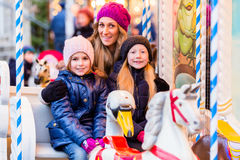 Familj som rider karusellen på julmarknad Royaltyfri Fotografi