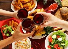 Familj som rostar vinexponeringsglas och har julmatställen Arkivfoto