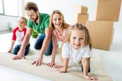 Familj som rullar ut matta arkivfoton