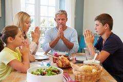 Familj som säger bönen, innan att tycka om mål hemma tillsammans Arkivbild
