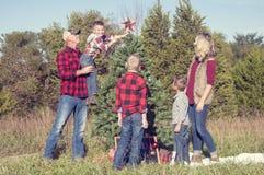 Familj som sätter stjärnan på julgranen Royaltyfri Foto