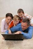 Familj som ser bärbar dator Fotografering för Bildbyråer