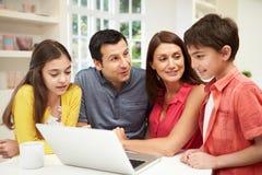 Familj som ser bärbara datorn över frukosten Arkivbild