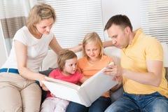 Familj som ser foto i Photobook arkivfoton