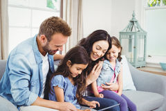 Familj som ser i digital minnestavla, medan sitta på soffan royaltyfria foton