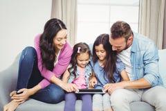 Familj som ser i minnestavladator, medan sitta på soffan Arkivfoton