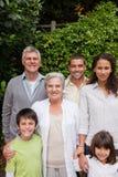 Familj som ser kameran i trädgården Royaltyfri Foto