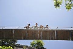 Familj som ser ner från bron mot klar himmel fotografering för bildbyråer