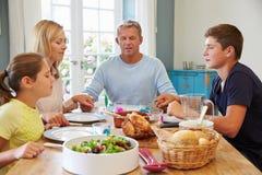 Familj som säger bönen, innan att tycka om mål hemma tillsammans Arkivbilder