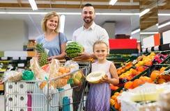 Familj som shoppar olika nya frukter i supermarket Arkivfoton