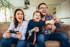 Familj som sitter på en soffa och spelar videospel och äter pizza arkivbilder