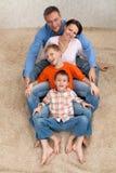 Familj som sitter på en vit matta Fotografering för Bildbyråer