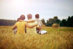 Familj som sitter på vetefält i solig dag fotografering för bildbyråer