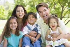 familj som sitter utomhus Arkivbild