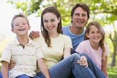 familj som sitter utomhus att le Royaltyfri Bild
