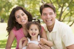 familj som sitter utomhus att le Fotografering för Bildbyråer