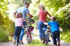 Familj som skjuter cyklar längs landsspår Arkivbild