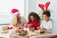 Familj som slår in julklappar på tabellen royaltyfri bild
