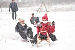Familj som sledding i vinter på snön Arkivbilder