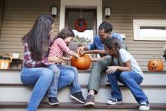 Familj som snider allhelgonaaftonpumpa på husmoment royaltyfri fotografi