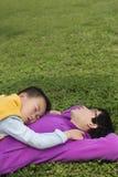 Familj som sover på gräsmatta Arkivbilder