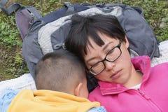 Familj som sover på gräsmatta Arkivbild