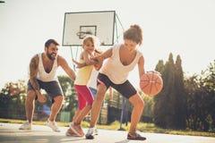 Familj som spelar basket tillsammans arkivfoto