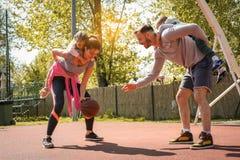 Familj som spelar basket tillsammans Uppfostrar bärande t Arkivfoto