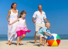 Familj som spelar bollen på stranden royaltyfria bilder