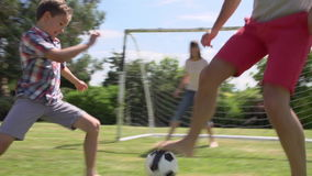 Familj som spelar fotboll i trädgård tillsammans arkivfilmer