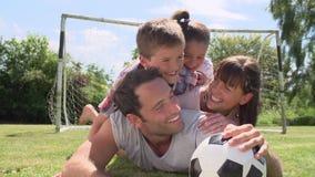 Familj som spelar fotboll i trädgård tillsammans