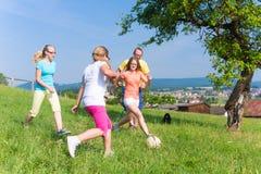 Familj som spelar fotboll på äng i sommar Arkivfoton