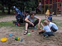Familj som spelar i sanden Arkivfoto