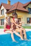 Familj som spelar i simbassäng. royaltyfri fotografi