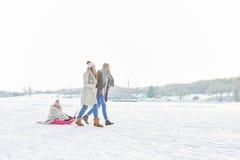 Familj som spelar kälken på snön fotografering för bildbyråer
