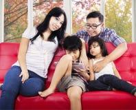 Familj som spelar leken på den digitala minnestavlan Royaltyfri Foto